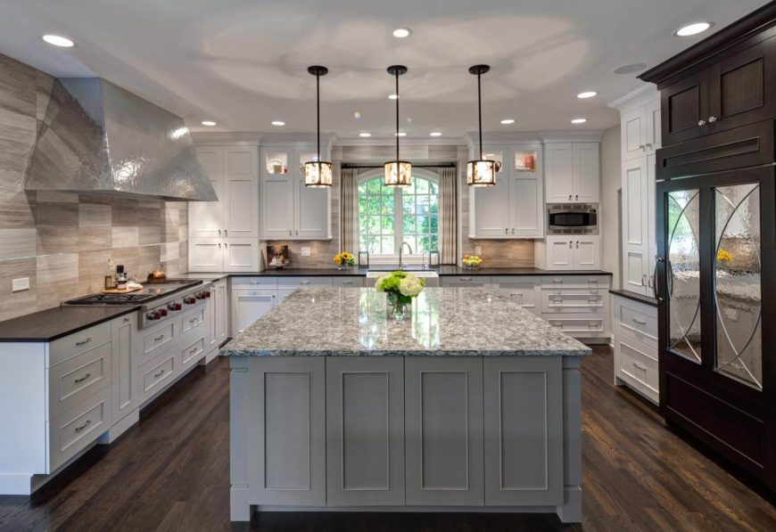 Here we have the functional cooking island at center, contrasting with the surrounding white cabinetry and black countertops beneath an array of cylinder chandeliers.