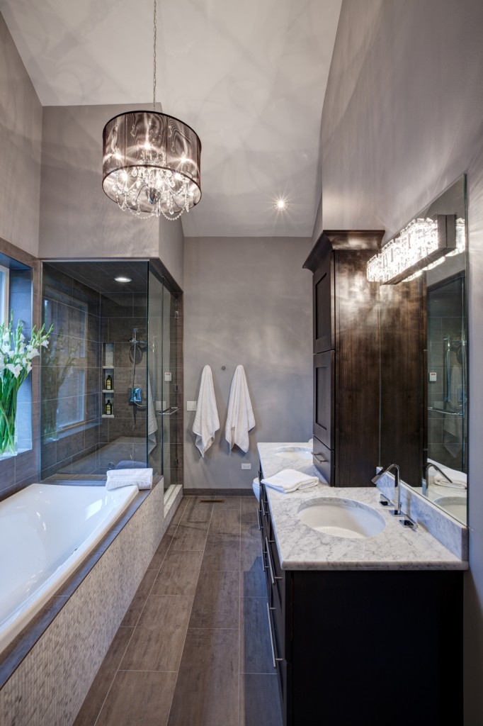 Fully enclosed glass steam shower and lengthy tub below a wide window sit across brown floor tiles from a large dark wood dual vanity with mirror mounted crystal sconces in this lengthy bathroom.