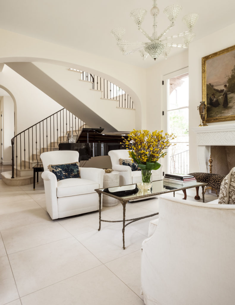 This room houses ample luxurious appointments, from white leather armchairs to the crystal chandelier, with a double wide arch leaving the staircase in full view.