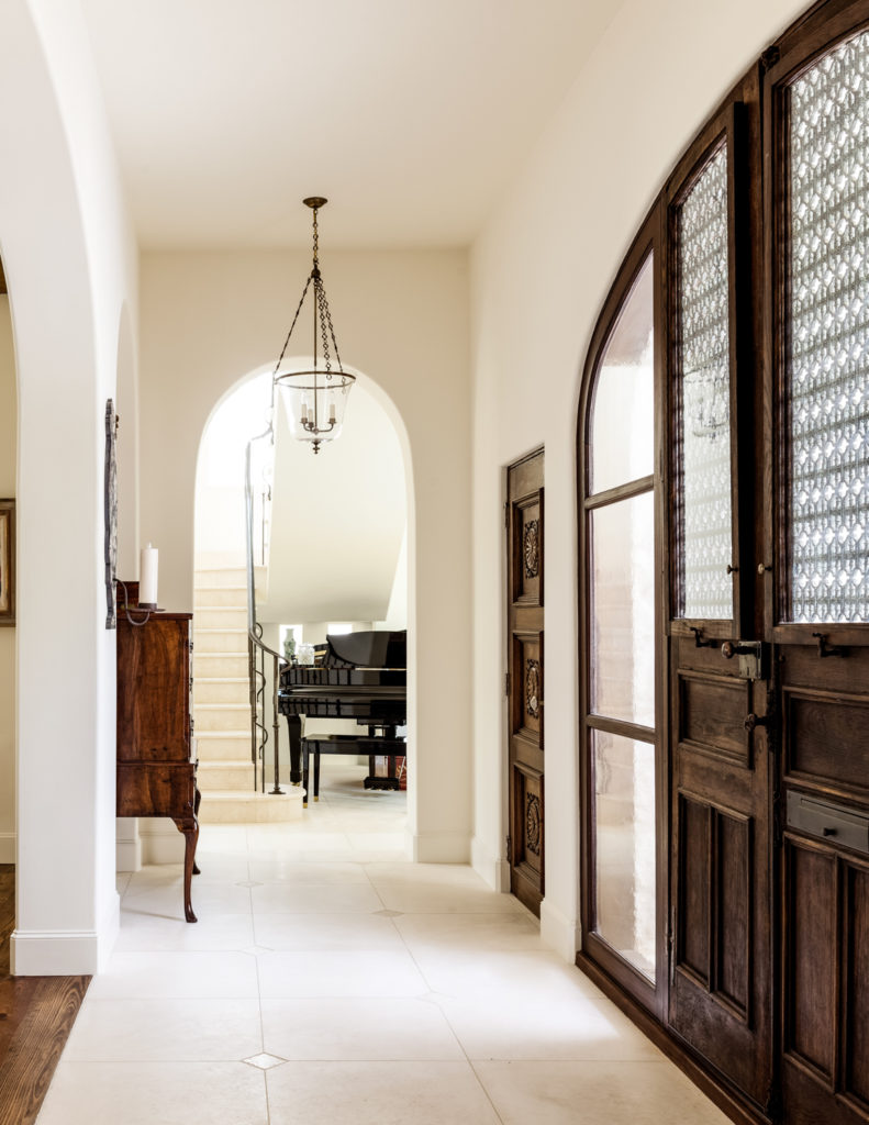 In the entryway, we see arched doorways leading in every direction. The main staircase begins at center, beside a black grand piano in a smaller family room.
