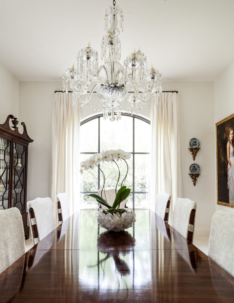 The dining room features extravagant details, including the massive chandelier at center, having over a crystal bowl holding orchids. The sleek dark wood table stands in the light of a nearly floor to ceiling arched window.