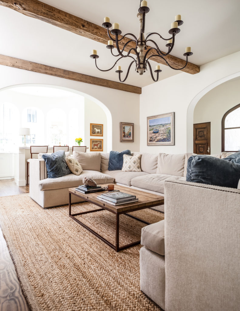 In the living room, we see a large U-shaped sectional on a tan area rug, wrapping around a rustic look hardwood topped coffee table.