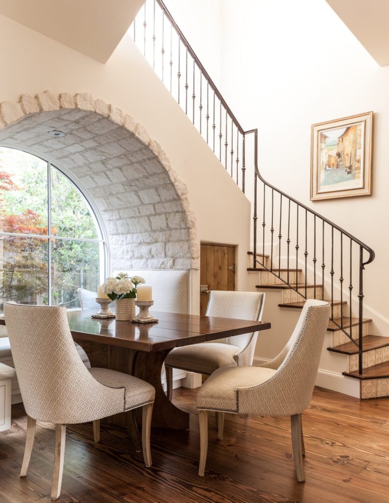 This cozy breakfast nook sits beneath the immense staircase, hugged by a stone brick arch and enjoying expansive views through the full height window.
