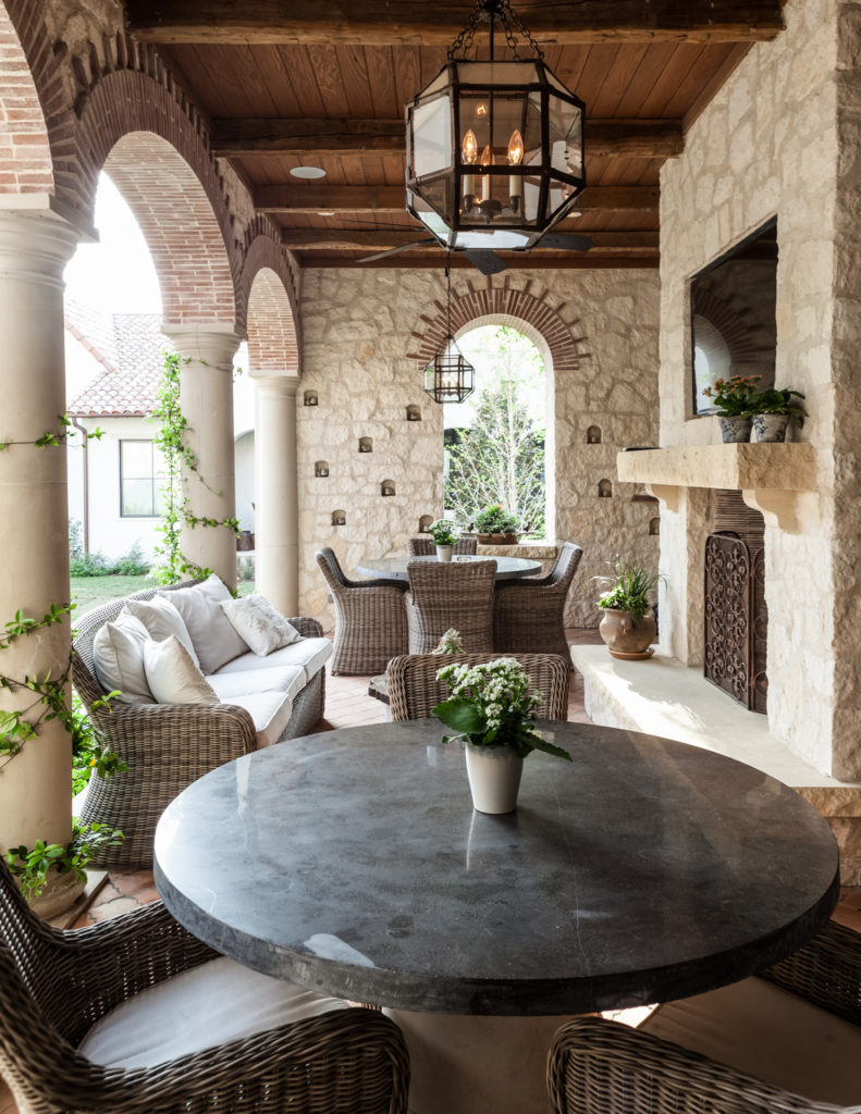 Moving outside, we see this heavily appointed patio, sheltered beneath a natural wood ceiling. Large stone fireplace overlooks two dining sets and an array of wicker frame, white cushion furniture.
