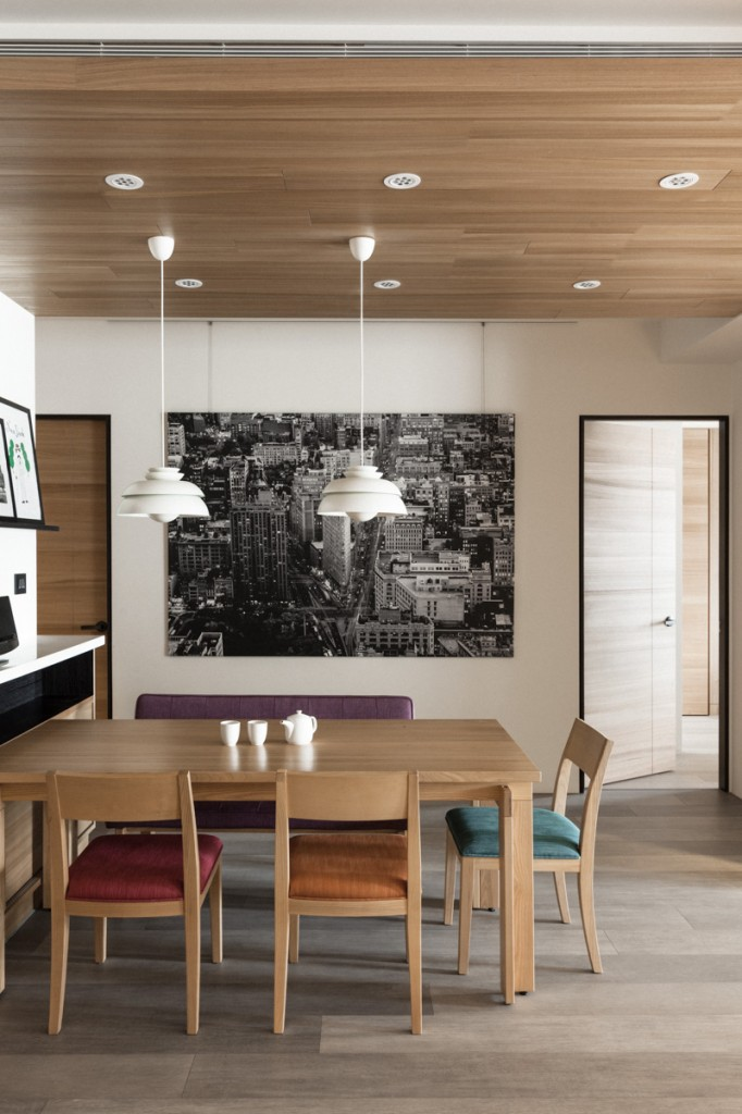 The dining table is surrounded by matching wood chairs with accent cushions in purple, red, orange, and blue for a burst of color amidst the neutral toned space. This area also holds a hardwood ceiling.