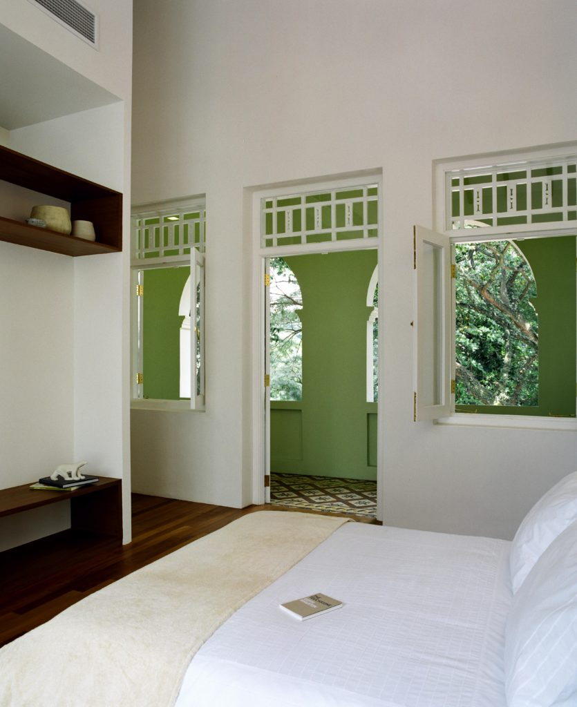 Bedroom in all white with dark hardwood flooring features a pair of natural wood shelves built into the wall, with windows opening onto the covered patio hall in green.