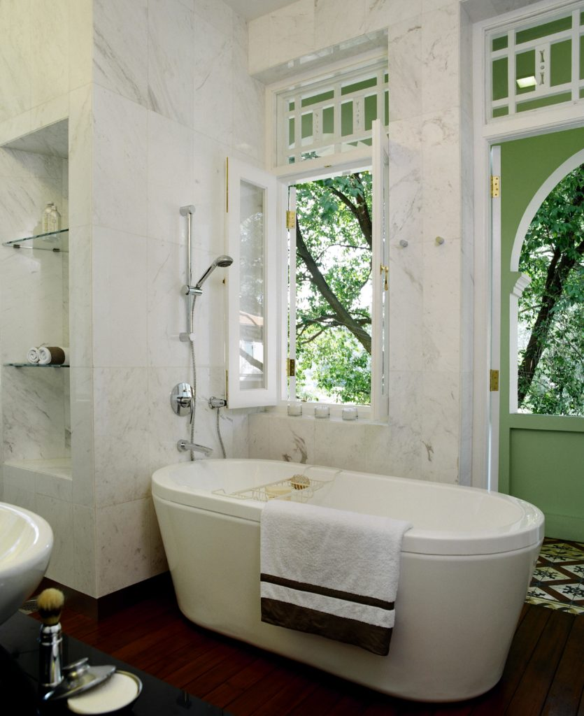 The pedestal tub stands next to window and door opening onto the upper level enclosed patio space.