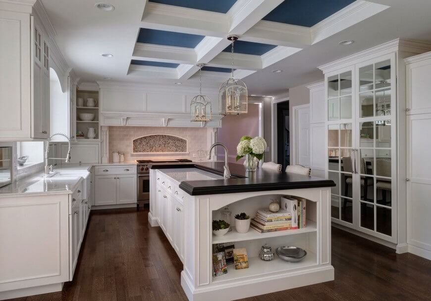 Kitchen in white stands an immense black-topped island below the detailed ceiling with blue inserts. Mirrored door refrigerator stands across the dark hardwood flooring, while white countertops stand in contrast with the island.