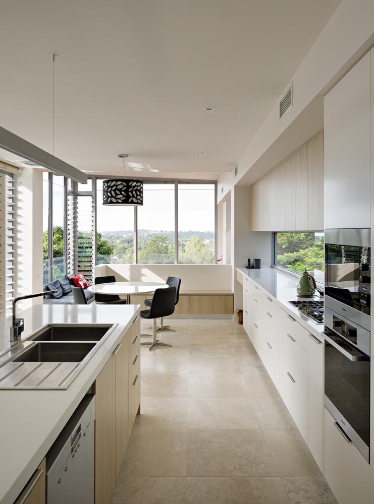 Next to the pool space, we have the minimalist, neutral toned kitchen. A mixture of white and natural wood toned cabinetry features throughout, with breakfast nook area surrounded by views of the valley beyond.