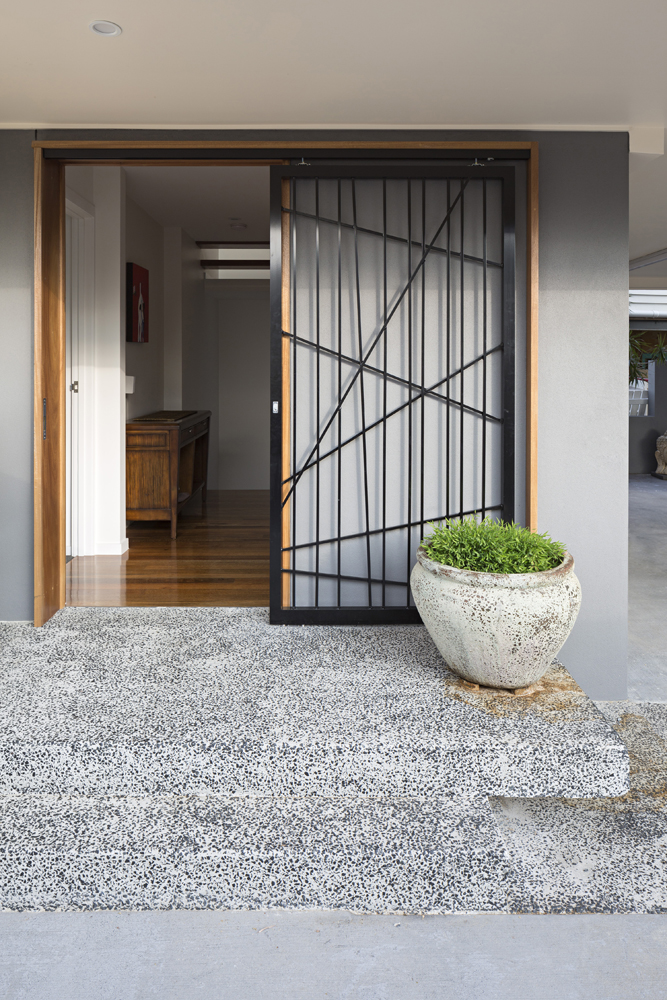 Front entrance: sliding black metal frame door with natural wood frame, standing over the stone steps and walkway.