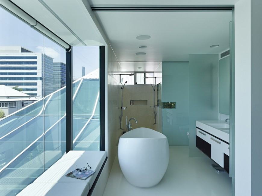 Bathroom features unique egg-shaped pedestal tub surrounded by layers of smoked glass. Window seating on white cushions at left, with walk in shower in background.