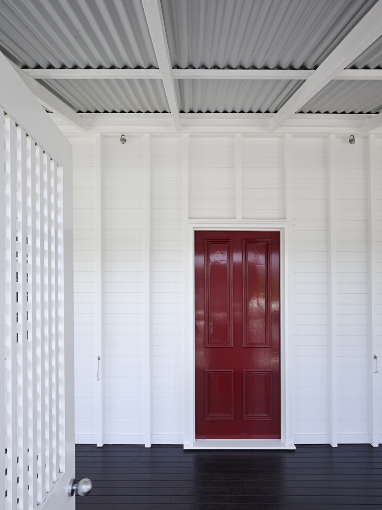Front door in striking red stands apart from the subdued direction of the surrounding home.