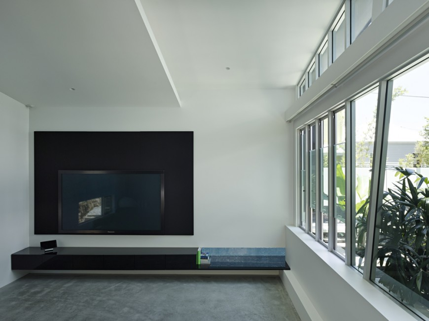Living room with minimalist design features black media surround for the television, with singular black shelf built into the wall. Angular window frames punctuate the wall of glass at right with views of rooftop garden.