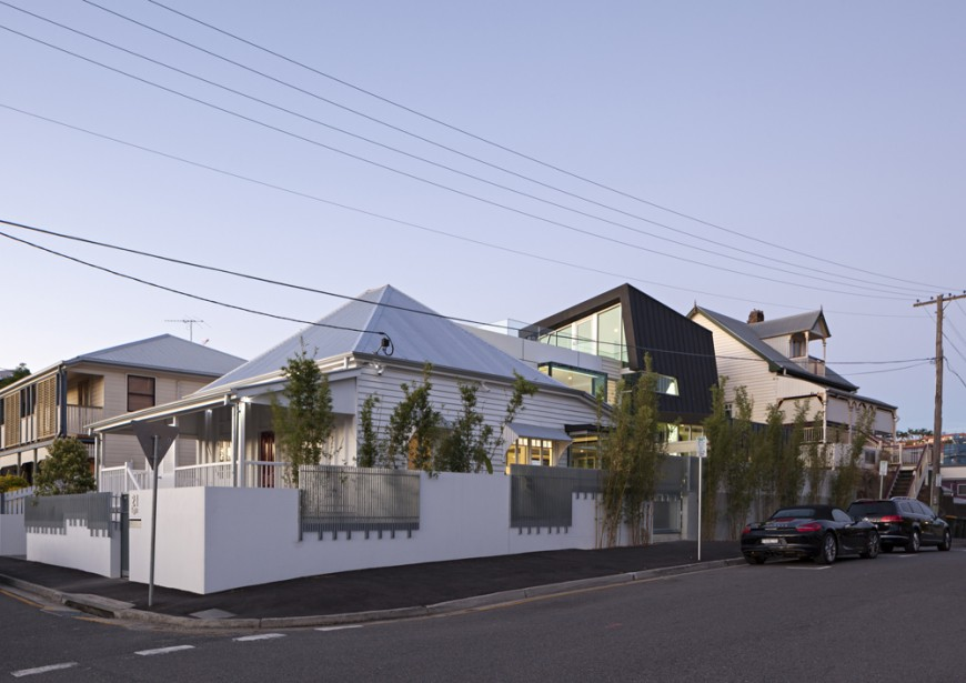 Streetside view reveals the original structure at left, with modern aluminum roof topping a traditional white body, with modern addition standing overhead to the right.