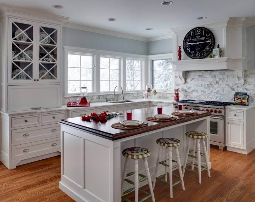 Bright tones feature throughout this kitchen, including white cabinetry and island, warm natural hardwood flooring, and stylized marble tile backsplash. Bold dark wood island countertop stands apart.