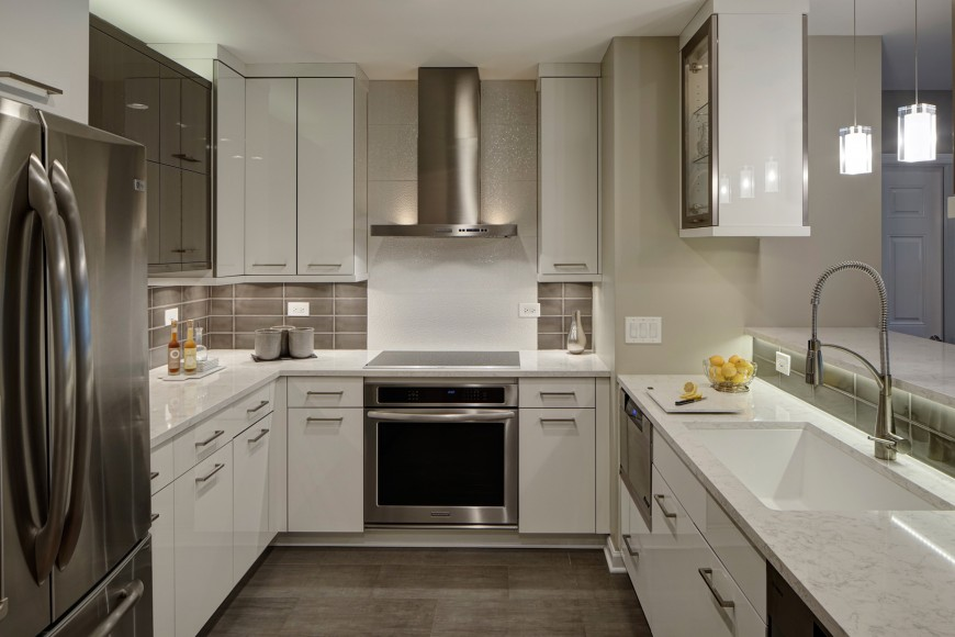 Another modern design, this kitchen features glossy white cabinetry, light marble countertops, and brushed steel appliances, along with under-lit tile backsplash.