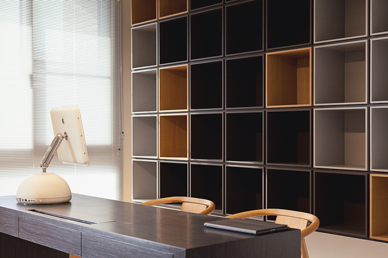 Behind the desk, we see a cubby wall, featuring cubic storage from floor to ceiling in a variety of wood tones.