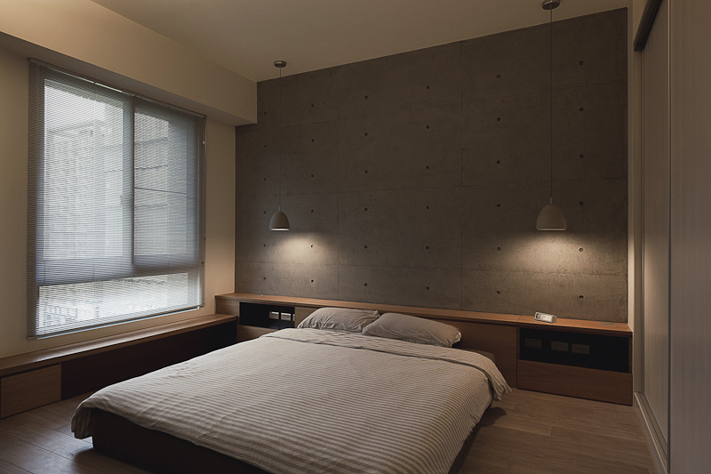 Master bedroom exemplifies the minimalist design, with low height built-in shelving on two full walls, creating a lengthy nightstand for the bed.