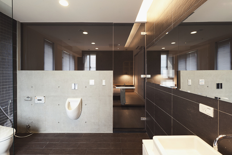 As part of the master bedroom suite, the bathroom is defined by a low concrete wall surrounded by glass panels, including door. Vanity mirror runs length of the space.