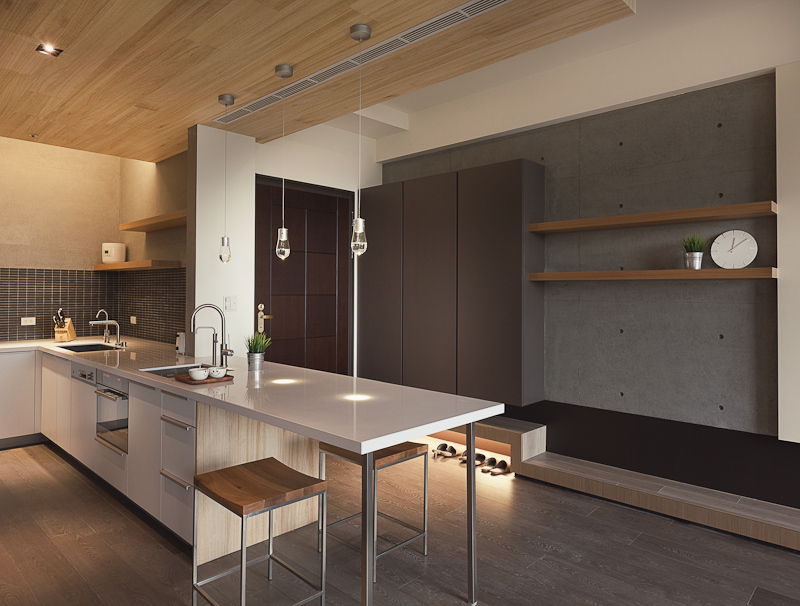 The open kitchen stands beside the main entryway. A subtle raised wood platform runs the length of the hall below cabinetry, with underside lighting for shoe storage. Glossy white kitchen counter extends into full dining space, with a pair of metal and curved wood bar stools below.