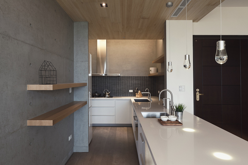 The lengthy countertop includes dual sinks, housing an array of sleek cabinetry below a dark tile backsplash. Simple natural wood plank shelving mounts on the concrete wall at left.