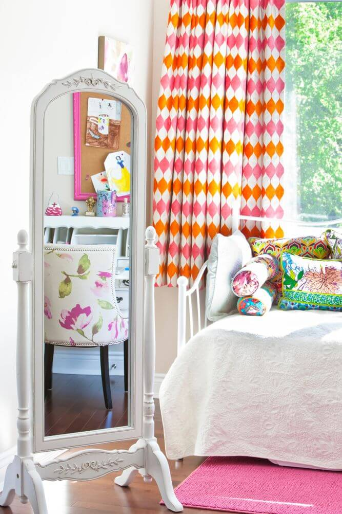 Traditional upright tilting mirror in wood frame stands next to window side daybed.