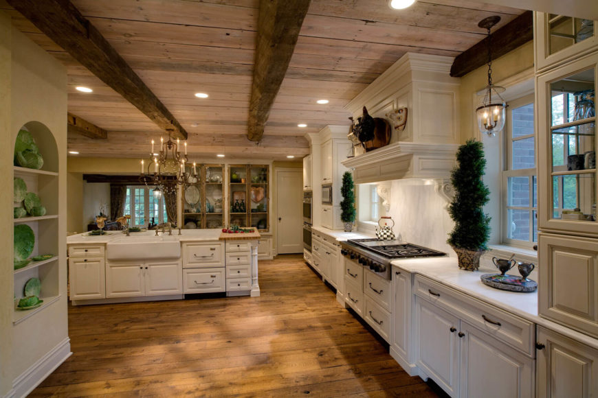 Expansive, rustic styled kitchen stands white cabinetry and modern appliances beneath a natural wood ceiling with exposed beams. White island with large built-in sink sits at center, with cutting board surface on one end.