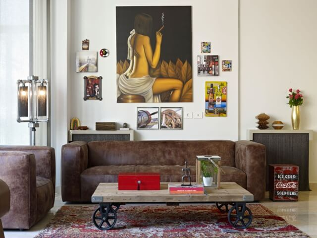The living room area is dominated by contemporary brown leather sofa and matching armchair, around a natural wood table with black wheeled feet. Paintings hang on the wall next to one of several recycled industrial furniture pieces, a pipe-based lamp.