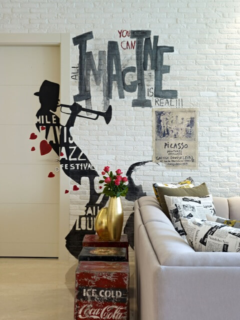 "The white brick walls hold numerous detailed personal touches, like this Miles Davis ""graffiti"" and Picasso art print. The lush white sofa is populated with newsprint style throw pillows."