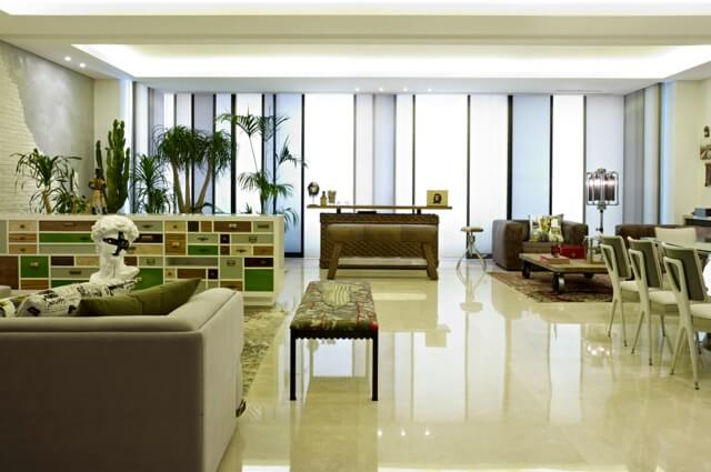 The entire space features light marble flooring, with colored shading on the floor to ceiling windows at far end.