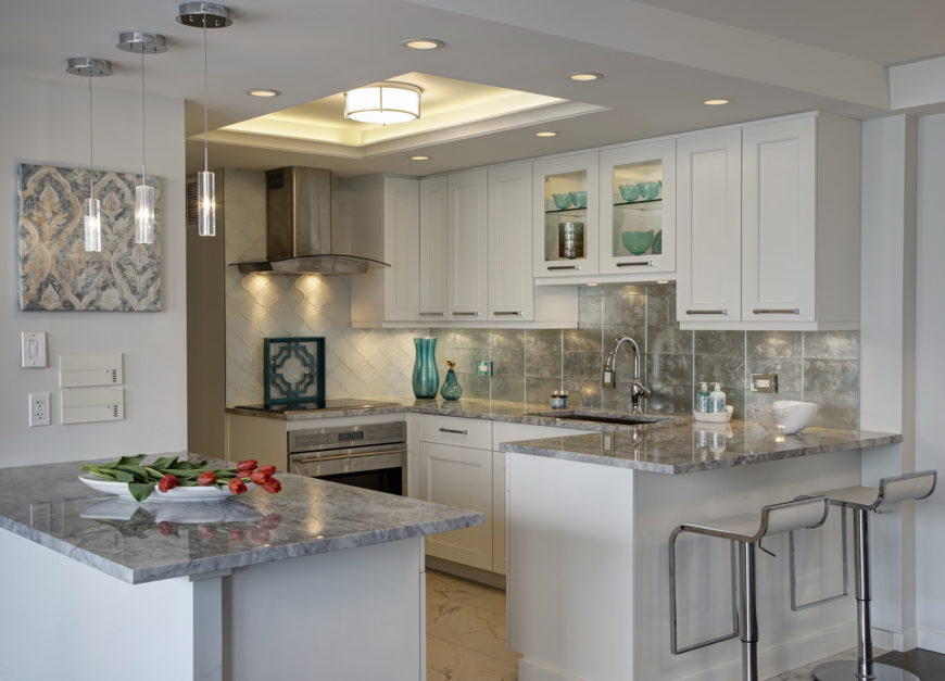 This cozy kitchen stands modern appliances and striking details, from chromatic backsplash to rich granite countertops, beneath an intricately detailed ceiling. Cutout at center holds a single cylindrical light, surrounded by an array of recessed lighting.
