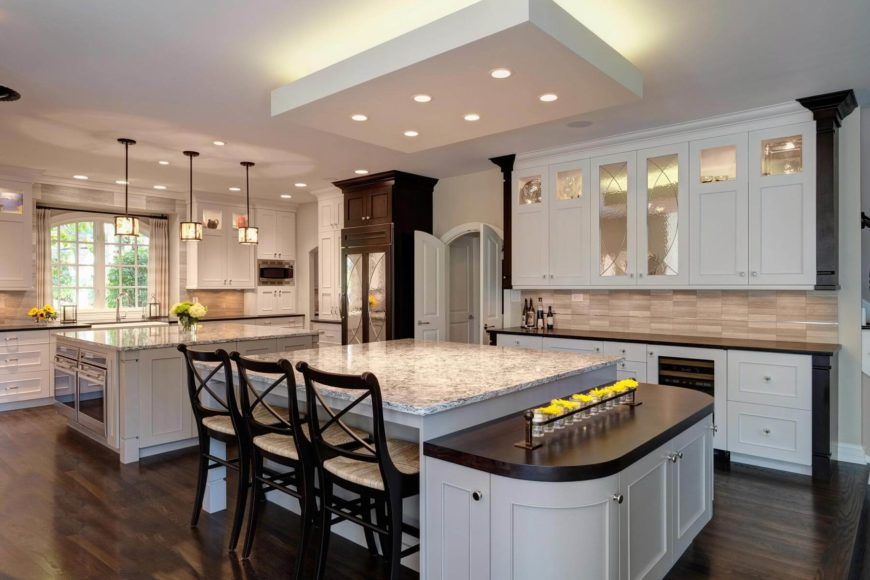 Massive open design kitchen holds two immense, marble topped islands. Foreground example features large square surface with bar style seating, plus lower rounded dark wood serving platform. Background island holds a pair of ovens beneath its expanse of countertop. Kitchen by Drury Design.