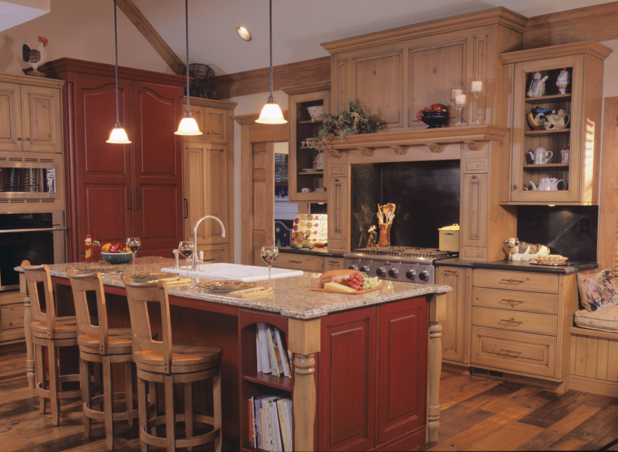 Here's another traditionally styled, natural material kitchen. Light wood cabinetry pairs with dark countertops and matching backsplash, while red wood island and single full height cabinet punctuates the neutral tones.