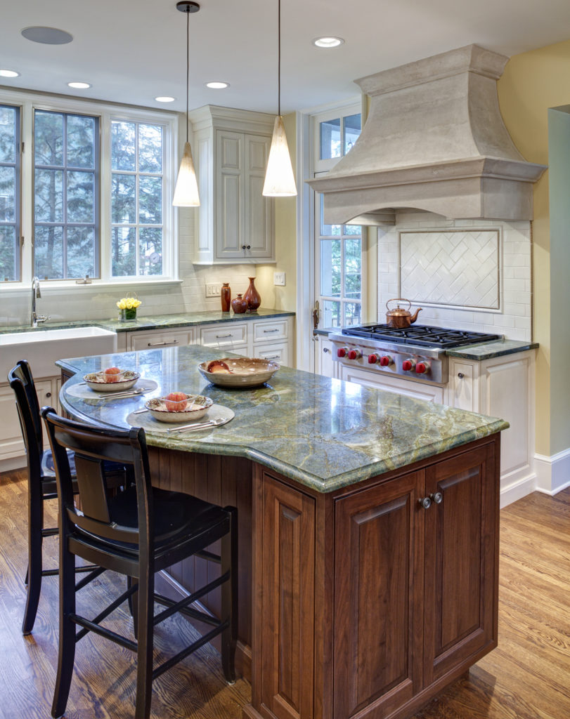 This cozy, bright kitchen in yellow and white features a standout island in rich, dark wood tone with green marble countertop, matching the surrounding counters. Light hardwood flooring, modern appliances, and white tile backsplash completes the look.