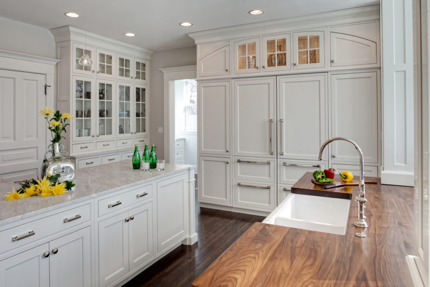 Here's another classically designed kitchen, standing an array of floor to ceiling white cabinetry over dark natural hardwood flooring. Island with light marble countertop stands across from natural wood countertop, with chrome fixtures all around.