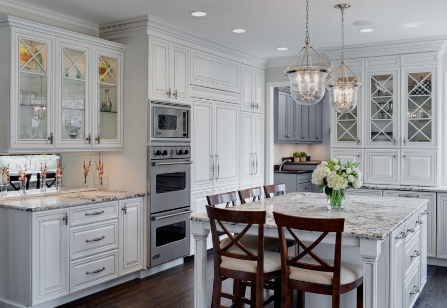A More Traditionally Styled Kitchen, Featuring Delicate Details Like The  Bell Chandeliers And Glass Door