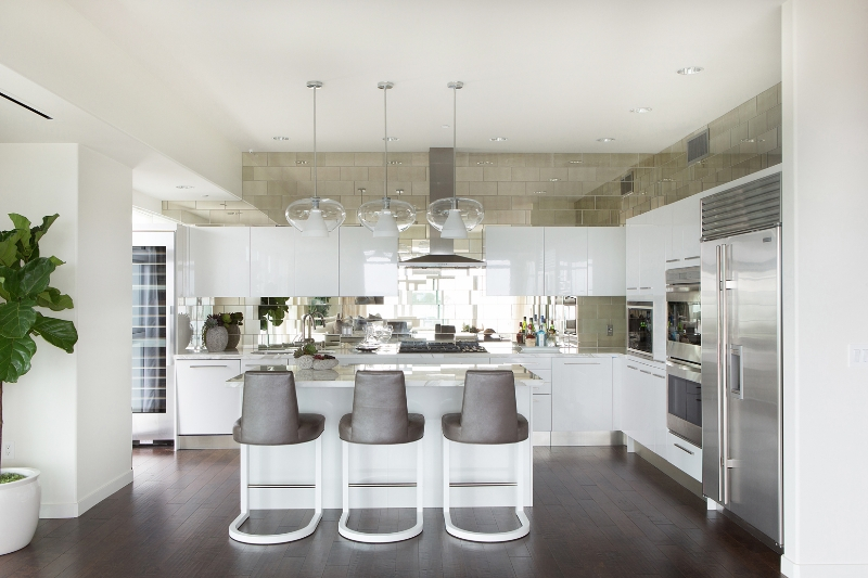 The kitchen, part of the large open central space, features glossy white cabinetry and mirrored tile backsplash, contrasting with the dark hardwood flooring. Glass sphere lighting, steel appliances, and island with dining space complete the look.