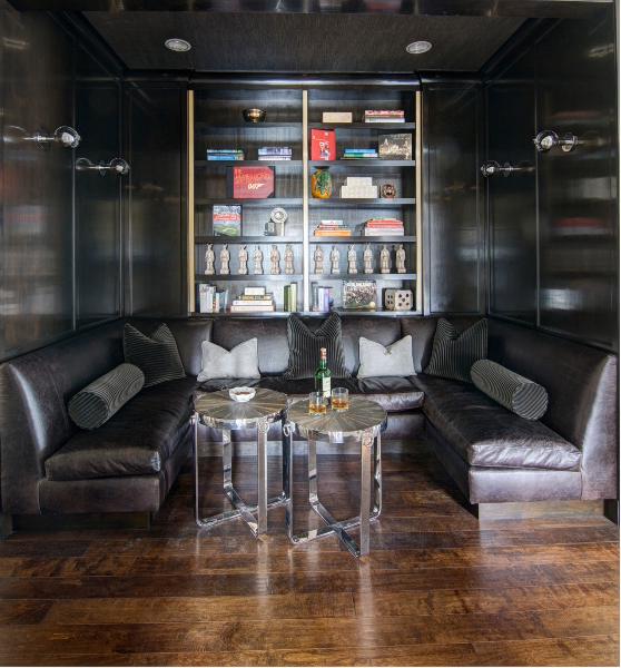 The home contains this lush, cozy seating cove, replete with U-shaped dark leather sectional hugging a pair of metallic drink tables.