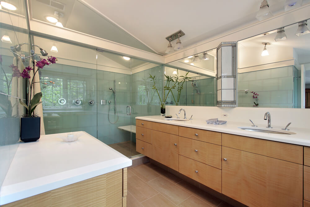 natural wood floating cabinetry hangs over tile flooring in this large vaulted ceiling bathroom