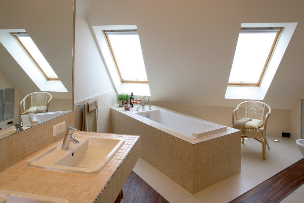 Angled Ceiling With A Pair Of Skylights Hangs Over Large Free Standing Soaking Tub Wrapped In