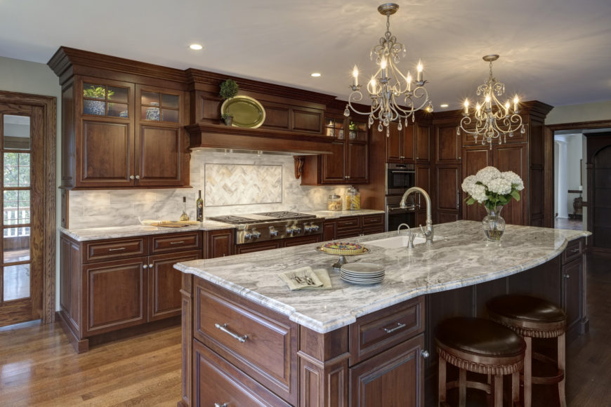 Natural dark hardwood cabinetry stands over lighter toned wood flooring, contrasted with light grey marble countertops and tile backsplash in this traditionally ornate kitchen.