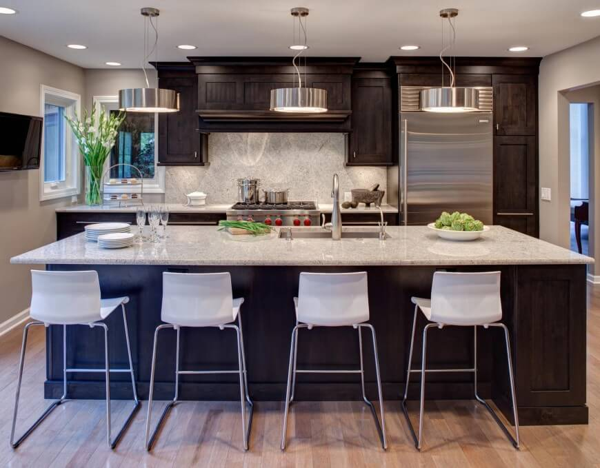 Contemporary styling informs this kitchen, featuring steel appliances and matching cylindrical trio of chandeliers over an immense marble topped island. Dark wood cabinetry features throughout.