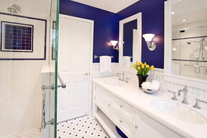 Open design vanity cabinetry features lower exposed shelving, while chromed sconces flank the white framed mirrors.