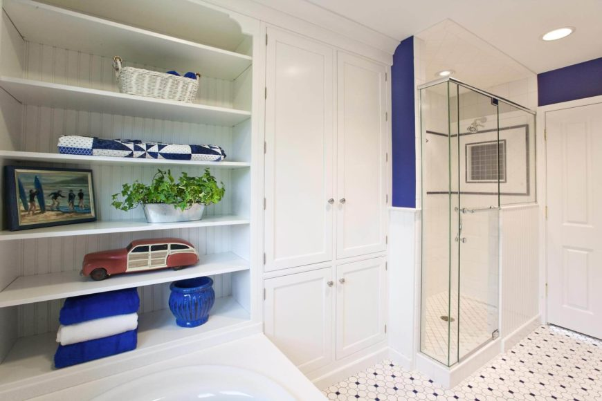 Full height cabinetry is sandwiched between the tub surface mounted open shelving and glass shower enclosure.
