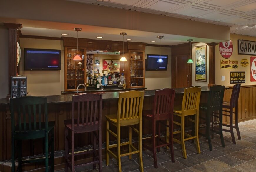 Full Fledged Home Bar Setting Includes Multicolored Light Shades And Bar Stools Paired With Dark Countertops