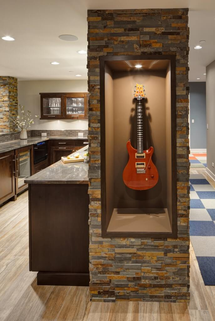 One of many custom touches, this display case for the owner's guitar is seated within one of the textured ledger stone columns.