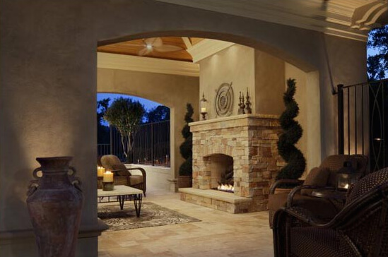 Wide Elliptical Archway Leads Out Into An Outdoor Covered Courtyard With A Stone Fireplace