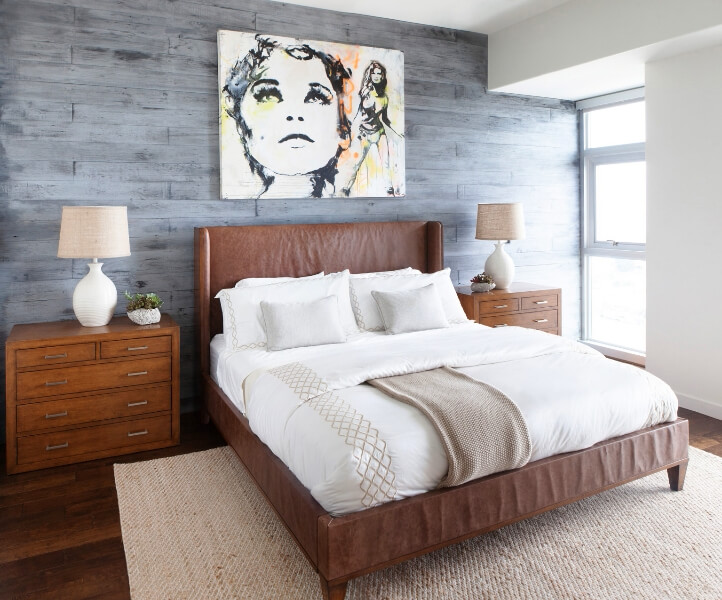 Leather bed with cream and beige bedding. Grey wood accent wall ...