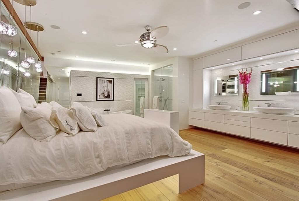 this modern master bedroom has an open plan on suite bathroom