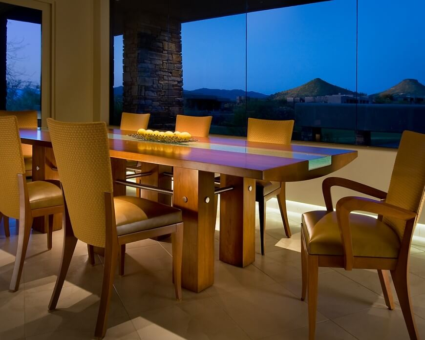 a sleek wood dining table with a glass center in front of a massive set of